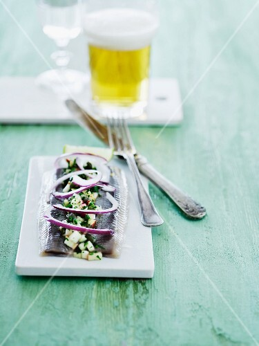 Soused herring with an apple dressing and red onion served with a glass of beer