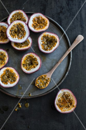 Halved passion fruits and a spoon of fruit flesh