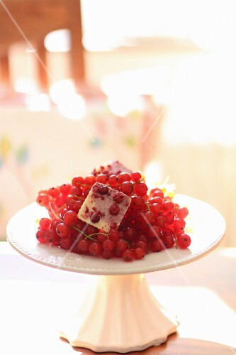Fresh redcurrants on a white cake stand
