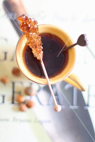 A rock candy stick on a cup of tea