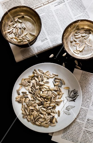Sunflower seeds on a plate and in a bowl on a newspaper