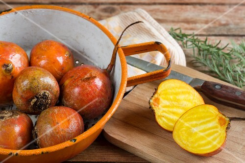 Freshly washed golden beets in a colander and one on a chopping board