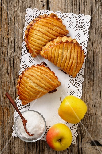 Apple turnovers, sugar and fresh apples on a doily