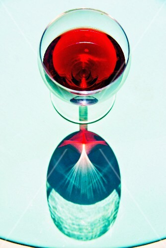 A glass of red wine reflected in a glass table