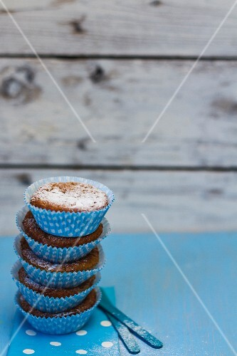 A stack of muffins with icing sugar in blue paper cases