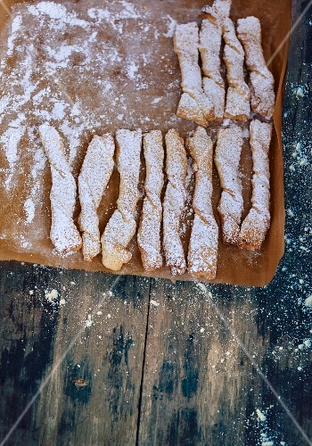 Puff pastry rolls with icing sugar on baking paper