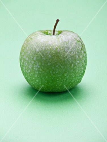 A green apple on a green surface