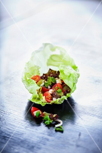 Tomato salad with feta cheese on a lettuce leaf