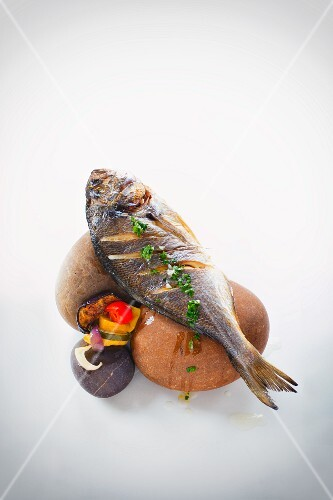 Baked seabream with vegetables on stones