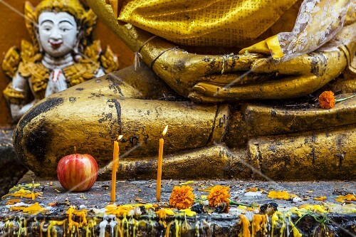 An apple, flowers and candles on a Buddha statue as offerings in a temple (Vientiane, Laos)