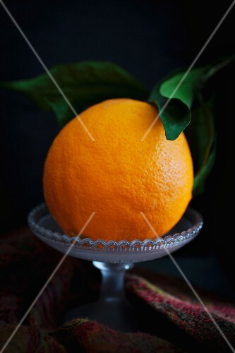 A Seville orange with leaves in a glass bowl