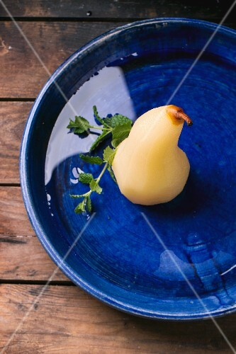 Pears poached in white wine with syrup and fresh mint in a blue ceramic bowl