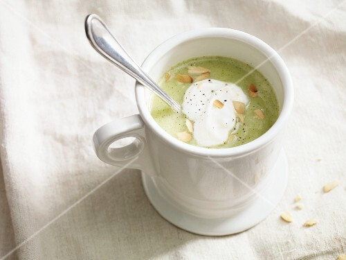 Cream of broccoli and potato soup with a dollop of cream and flaked almonds