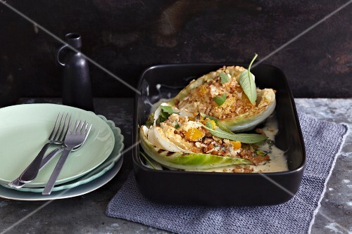 Oven-roasted pointed cabbage filled with couscous on a cheese sauce