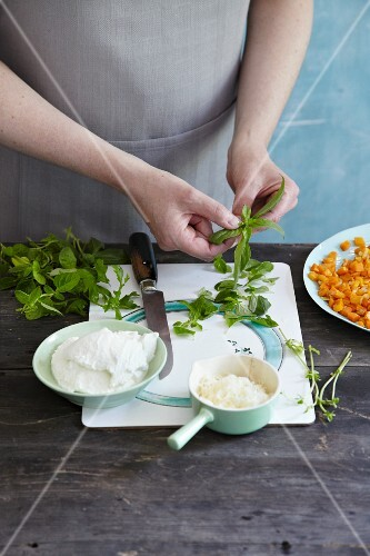 Fresh herbs being prepared for a crespelle filling