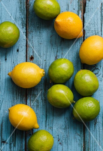 Lemons and limes on a blue wooden surface