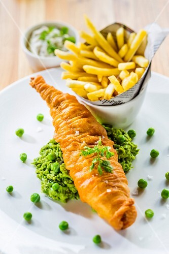 Battered fish on a bed of mushy peas with chips