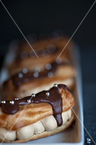 Chocolate covered eclairs with silver pearls and coffee cream