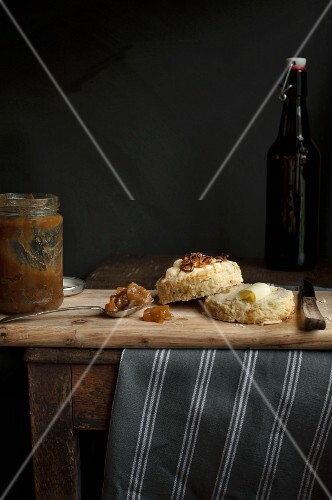 A halved onion and cheese scone, with butter, on a wooden board with a jar of apple chutney