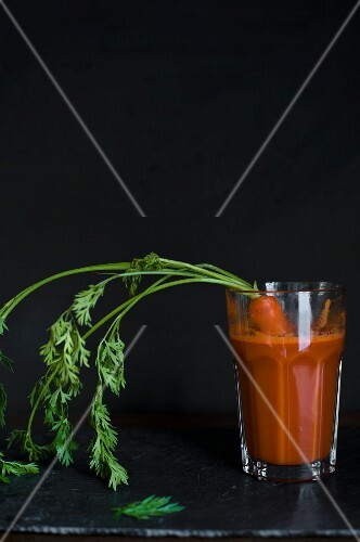 A glass of carrot juice with a fresh carrot