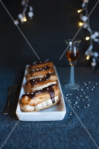 A chocolate covered eclair with silver pearls and coffee cream next to a glass of sherry (Christmas)
