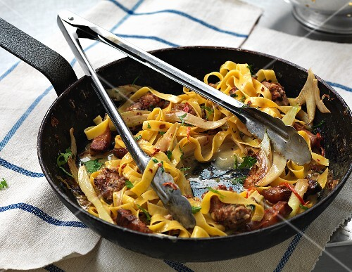 Tagliatelle with sausage and cheese in a pan