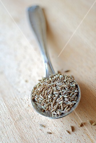 Cumin seeds on a silver spoon