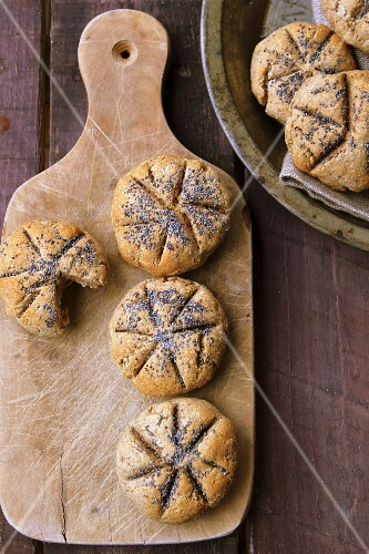 Rye bread rolls with poppy seeds on a chopping board
