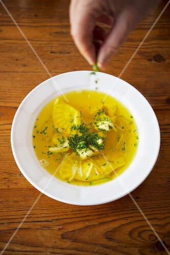 Fish soup with sage ravioli being sprinkled with herbs