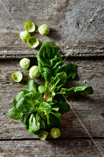Organic spinach, lamb's lettuce and Brussels sprouts on a wooden surface
