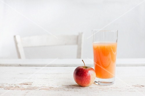 A glass of fruit juice and an apple on a white wooden table with a chair