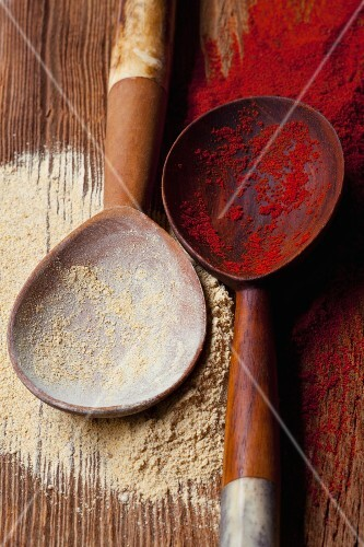 Curry powder and paprika powder on wooden spoons