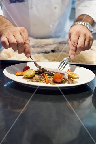 Gerd Kastenmeier preparing branzini in a salt crust on a plate