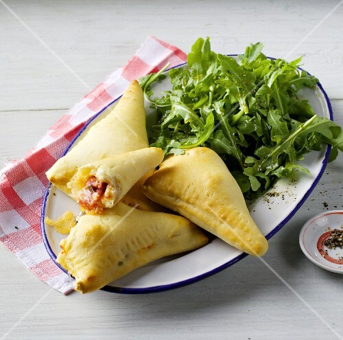 Pizza pockets filled with salami and sardines served with fresh rocket