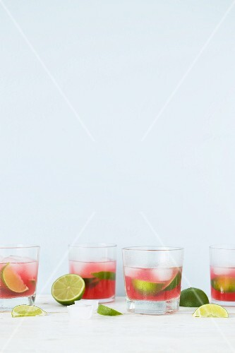 Pink summer drinks with limes and ice cubes