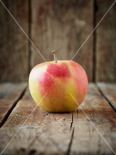 A red and yellow apple on an old, brown wooden surface in front of a wooden wall