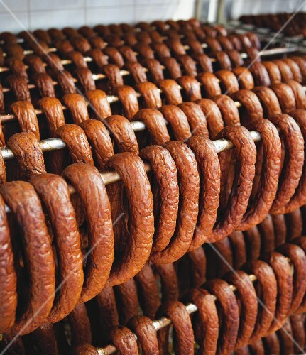 Lots of sausages hanging on a metal rack