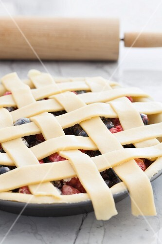 An unbaked berry pie with a lattice lid