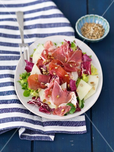 A mixed lettuce with melon, ham and sunflower seeds