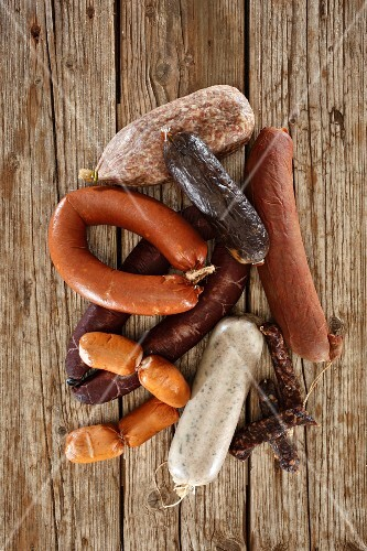 Various sausages on a wooden surface