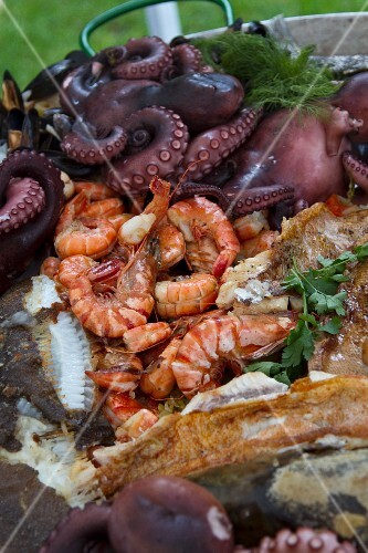 Fried fish, prawns and octopus in a bowl in a garden
