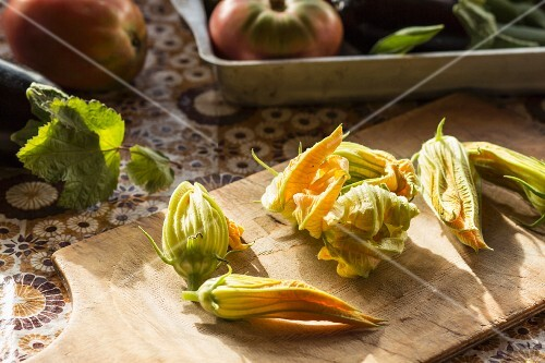 Courgette flowers on a wooden chopping board