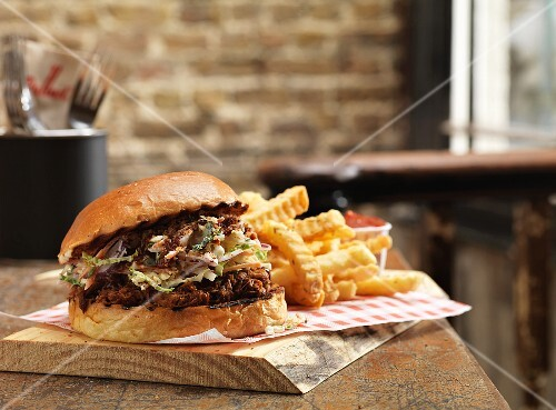A pulled pork burger and chips on a rustic wooden board