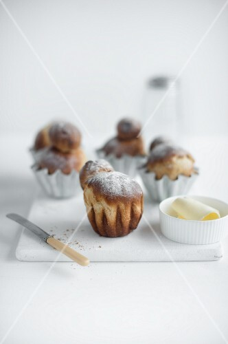 Brioches on a white chopping board with a knife and a butter dish