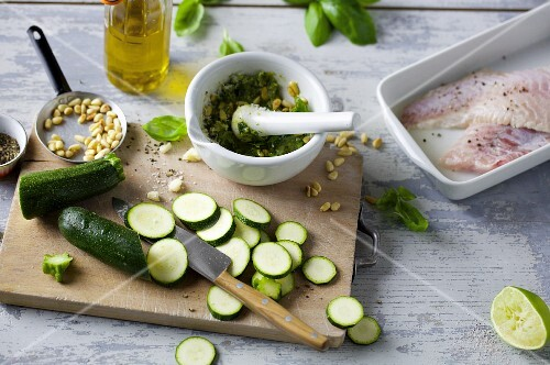 A kitchen scene with pesto, fish and courgette