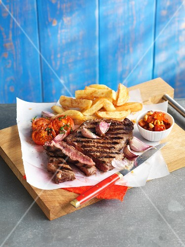 Grilled beef steak with chips and tomatoes