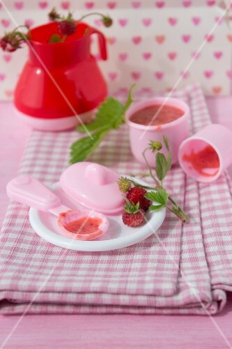 Wild strawberries with sugar and condensed milk served on a dolls' tea set