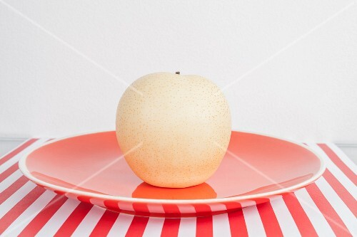 A nashi pear on a red plate