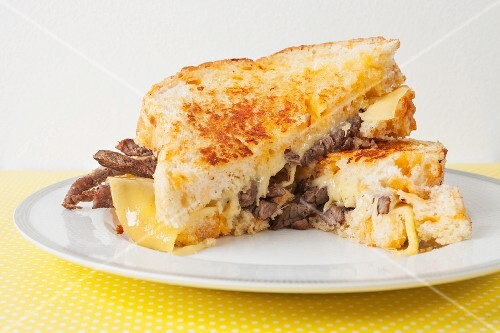 A toasted sandwich with steak and Gouda cheese
