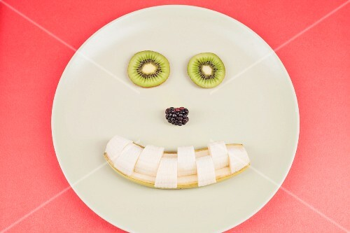 A smiley face made from of kiwi, blackberries and a banana
